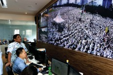 Closely: Acting Jakarta Governor Sumarsono [left] observes thousands of Muslims praying on Friday from the Jakarta Smart City center at City Hall. JP Seto Wardhana