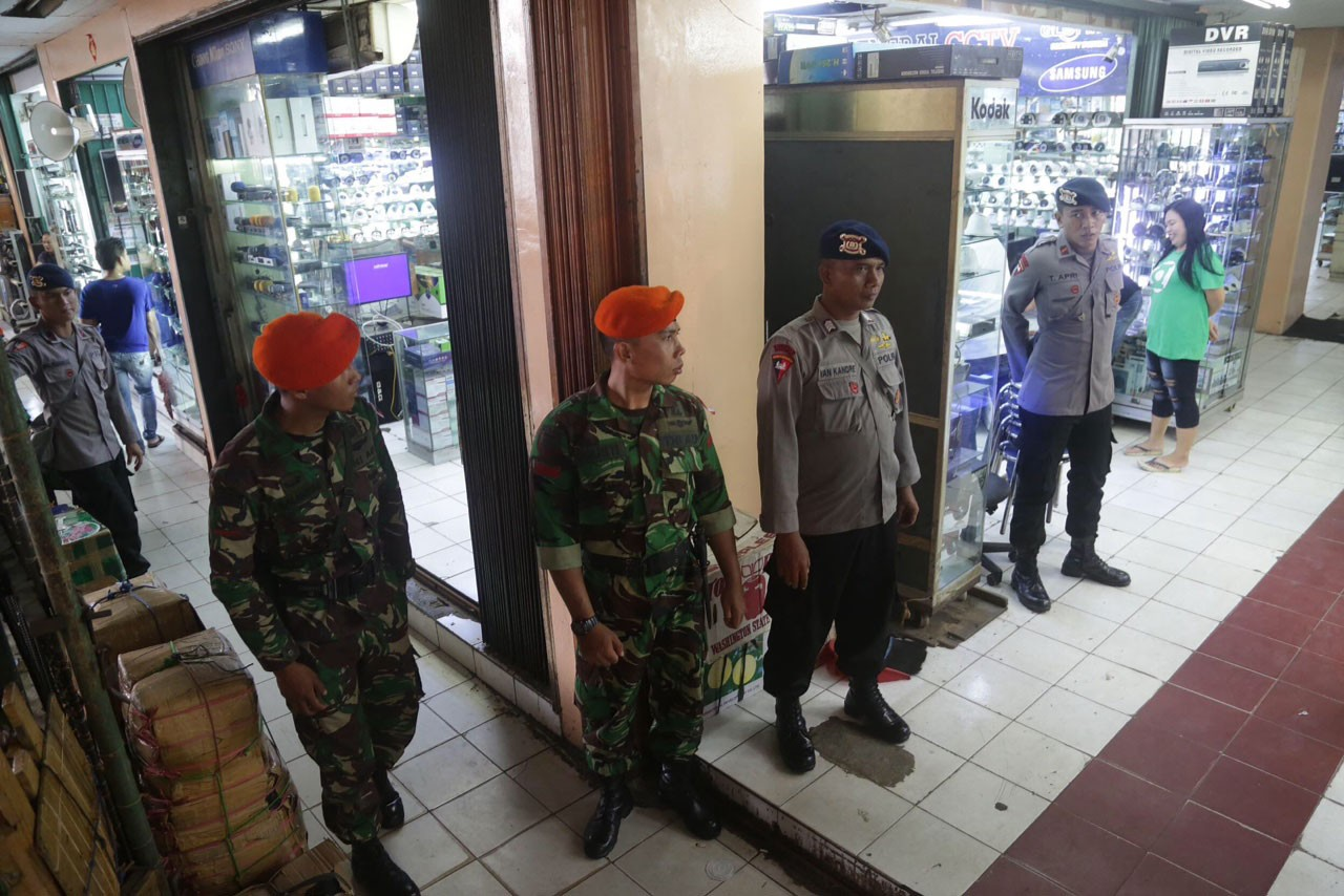 On alert: Military and police personnel stand guard at a Glodok shopping arcade in West Jakarta. Business activities ran as usual but shops were quieter than on typical days. JP/ Wendra Ajistyatama