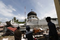 Residents observe a damaged mosque in Pidie Jaya, Aceh. An earthquake that measured 6.5 on the Richter scale hit several regencies in Aceh on Dec. 7 at 5:03 a.m. local time. At least 94 people were killed because of the quake. JP/ Hotli Simanjuntak