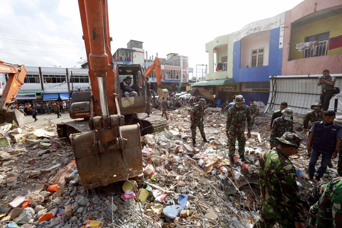 Rescuers use excavators to search for victims under the rubble of collapsed buildings after an earthquake in Pidie Jaya, Aceh. JP/ Hotli Simanjuntak