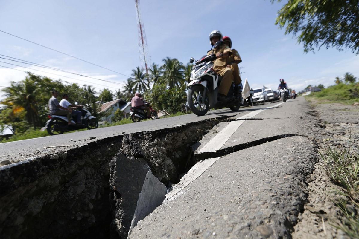 Motorcycles pass a damaged road caused by a strong earthquake in Pidie Jaya regency, Aceh. JP/ Hotli Simanjuntak