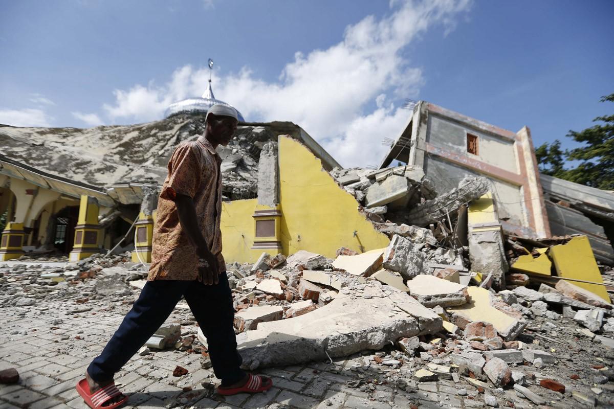 A man walks past a collapsed mosque in Pidie Jaya on Dec. 7. Several regencies in Aceh were hit by the quake but Pidie Jaya experienced the heaviest impact. JP/ Hotli Simanjuntak