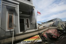 A national red-and-white flag flies over a collapsed building at Meureudu Market in Pidie Jaya regency, Aceh. JP/ Dhoni Setiawan