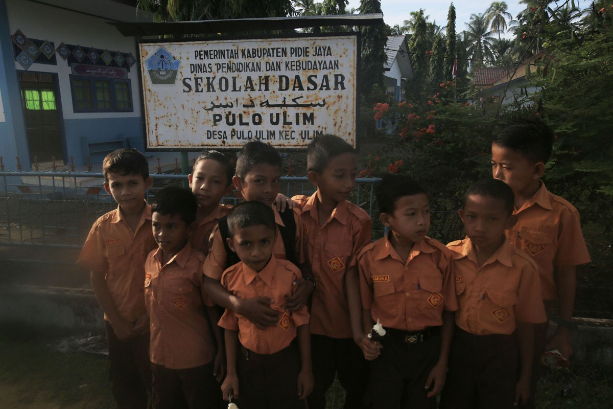 Students of Pulo Ulim elementary school in Pidie Jaya regency, Aceh, stand in front of their school's sign on their first day back in class after the Dec. 7 earthquake. JP/ Dhoni Setiawan
