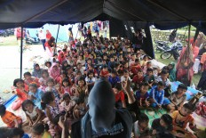 A counselor from the Social Affairs Ministry cheers up children at an evacuation camp in Meunasah Jurong village, Pidie Jaya regency, Aceh on Saturday, 10 December 2016. JP/ Dhoni Setiawan
