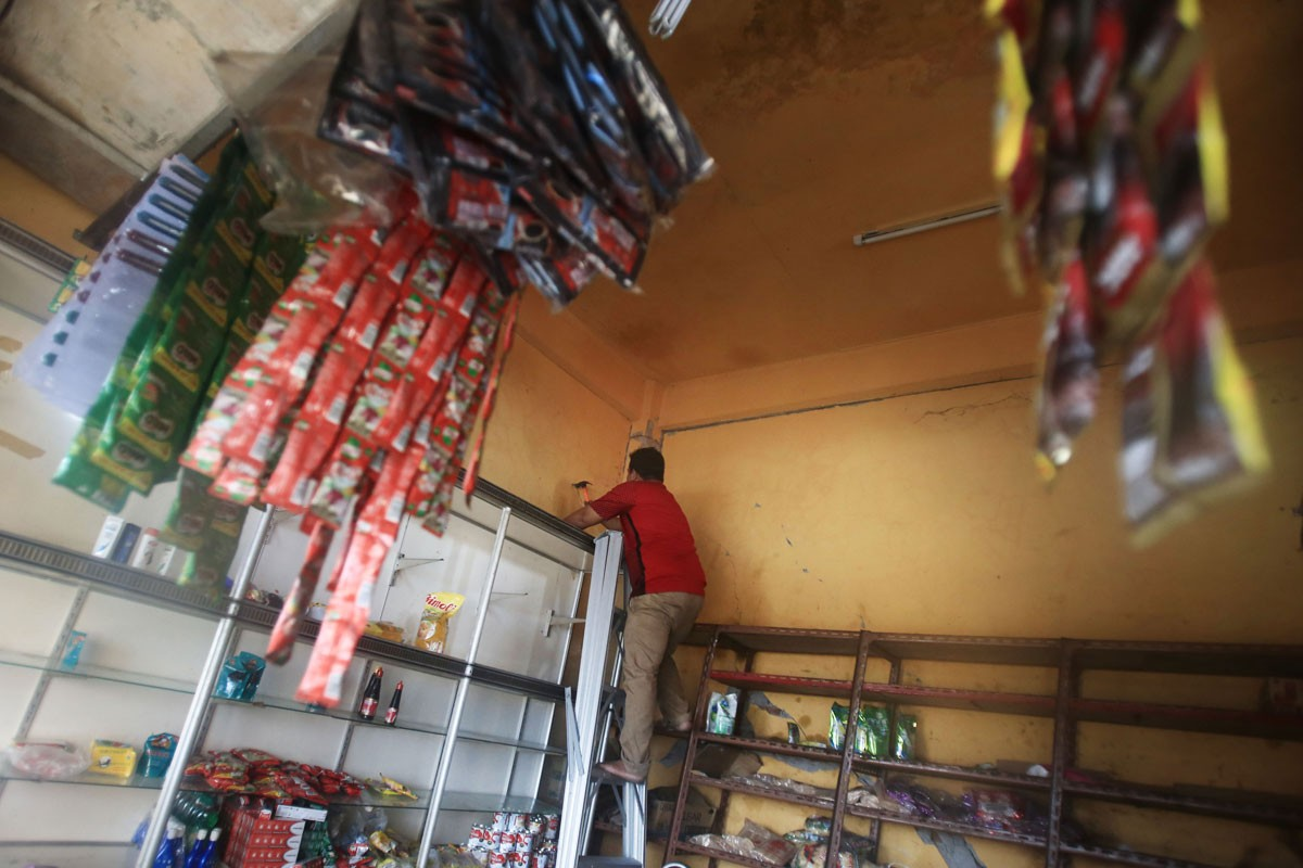 A man repairs damage at his store caused by the Dec. 7 earthquake. JP/ Dhoni Setiawan