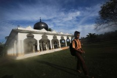 An elementary student passes by a mosque to go to his school in Pidie Jaya regency, Aceh, on Saturday, 10 December 2016. JP/ Dhoni Setiawan