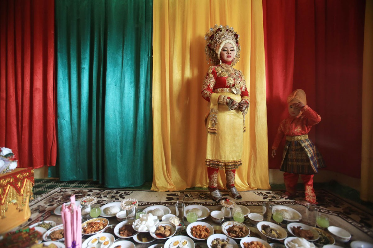Rohimah (left) prepares to welcome her husband-to-be and his family members for a modest wedding celebration at her house in Meunasah Jurong village, Pidie Jaya regency, Aceh, on Saturday, 10 December 2016. JP/ Dhoni Setiawan
