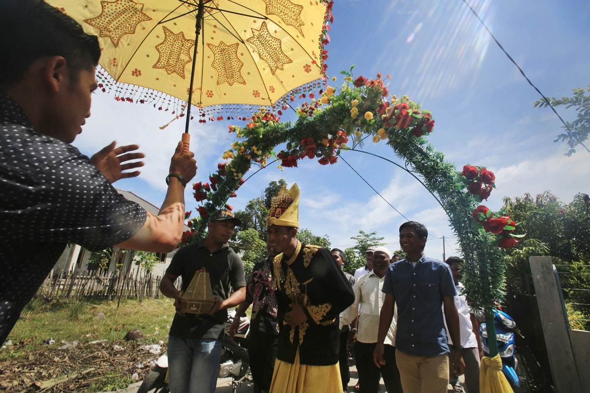 Zulkarnaen (center) and his family members arrive at the house of his bride-to-be in Meunasah Jurong village, Pidie Jaya regency, Aceh. The groom wears the traditional wedding attire of Aceh. JP/ Dhoni Setiawan