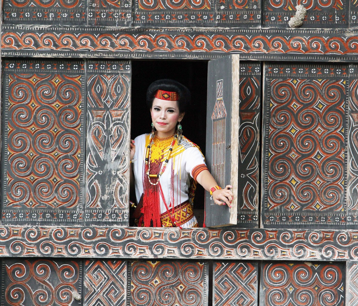 Opening up: A Torajan woman poses from inside a Tongkonan traditional house in Suloara' village. JP/ PJ Leo