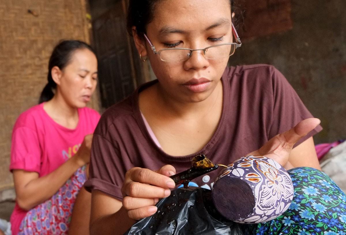 Artisans use a canting or spouted bowl to create batik patterns on pottery in a workshop in Jarum village, Bayat district, Klaten, Central Java.  JP/Ganug Nugroho Adi