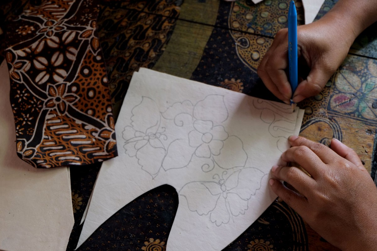 An artisan draws the batik pattern he will apply to his pottery. JP/Ganug Nugroho Adi