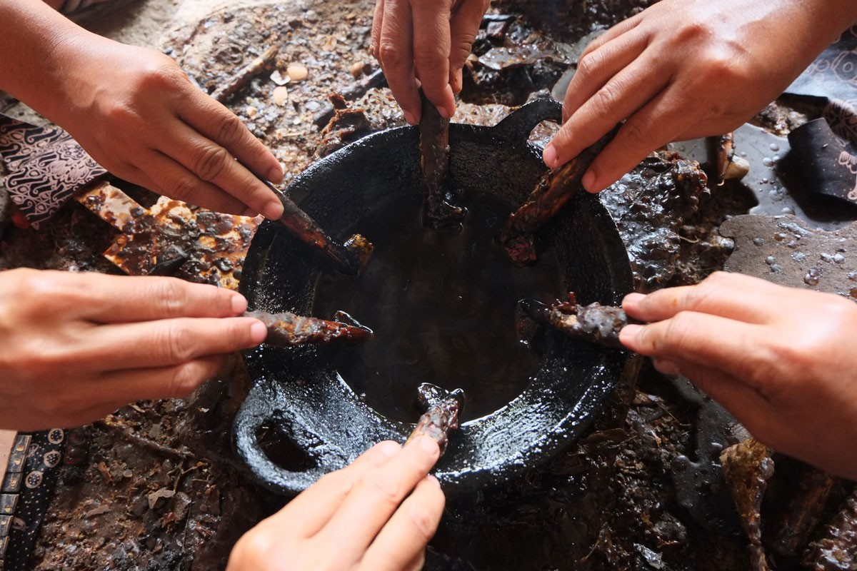 Craftswomen take hot wax from a small wok using a canting [spouted bowl]. JP/Ganug Nugroho Adi