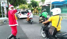 A traffic control volunteer dressed as Santa Claus directs traffic at Jl. Wora Wari, Surakarta, Central Java. He wears the unique costume to celebrate Christmas day. JP/Ganug Nugroho Adi