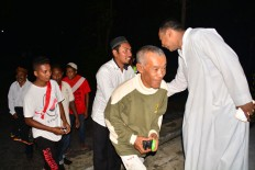 Rev. Hieronimus Jelahu [right], a Catholic priest of Santo Arnoldus and Yoseph Waelengga Church, Ruteng, Flores East Nusa Tenggara, greets young people from the Baturrahman Waelengga Mosque after the Christmas Eve mass on Saturday night. The youth of Baturrahman Mosque were involved in securing the area around the church during Christmas mass.JP/Markus Makur