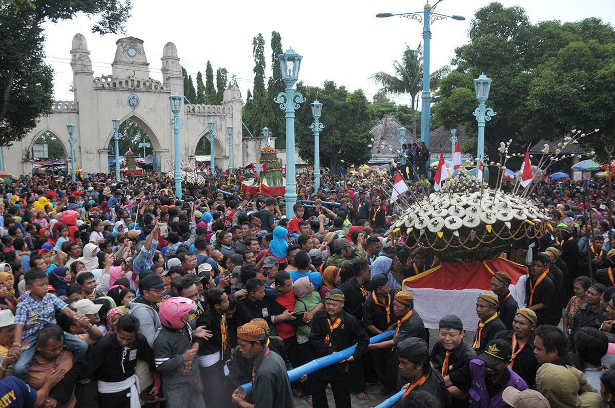 Hundreds of people struggle to obtain a piece of the gunungan, the cone shaped offerings, in front of the Surakarta Grand Mosque. JP/Ganug Nugroho Adi