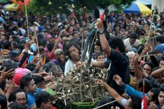 People fight to grab a piece of the gunungan, or cone shaped offerings, in front of the Surakarta Grand Mosque. JP/Ganug Nugroho Adi