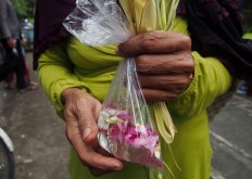 A Surakarta resident carries a plastic bag containing water and flower petals as an offering in a ritual called Miyos Gongso. JP/Ganug Nugroho Adi