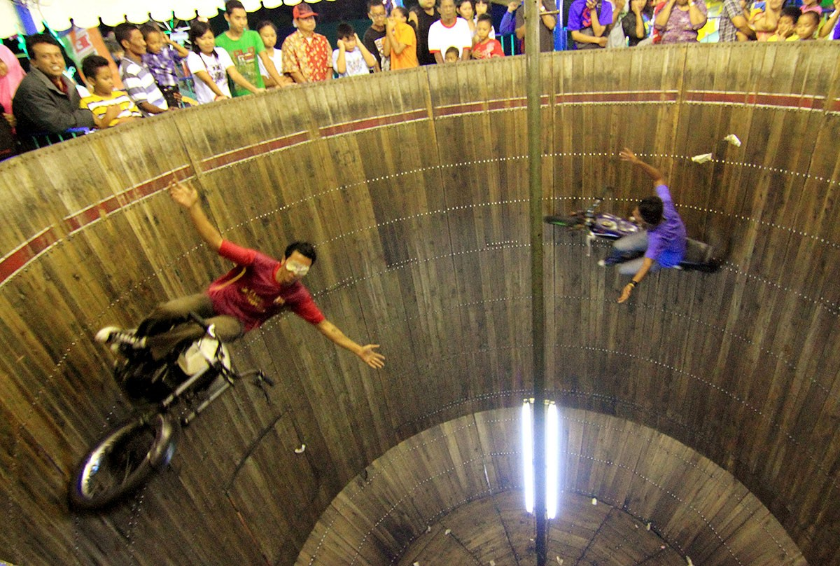 "Two daredevils ride their motorcycles at high speed on the inside of a barrel in an adrenalin-boosting attraction called ""Tong Setan"". JP/Ganug Nugroho Adi"