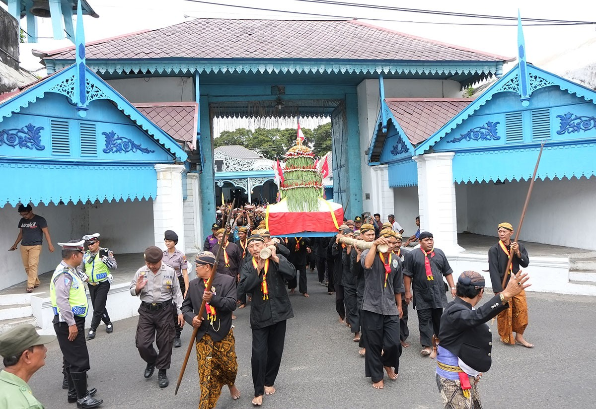Royal servants and soldiers of the Kasunanan Palace, Surakarta, bring gunungan [cone shaped offerings], which contain vegetables, fruits, harvest yields and rengginang [sticky rice-based traditional snacks]. JP/Ganug Nugroho Adi