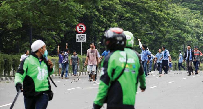 Transportation clash: Online motorcycle taxi drivers clash with protesters in an incident in Jakarta on March 22. Thousands of conventional taxi drivers took to the streets to protest against the operation of mobile phone-hailing transportation apps.