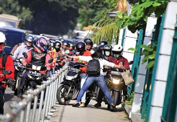 No way: Pedestrian Alfini, 34, boldly blocks motorcyclists trespassing on a sidewalk on Jl. Sudirman, Central Jakarta, on May 2.