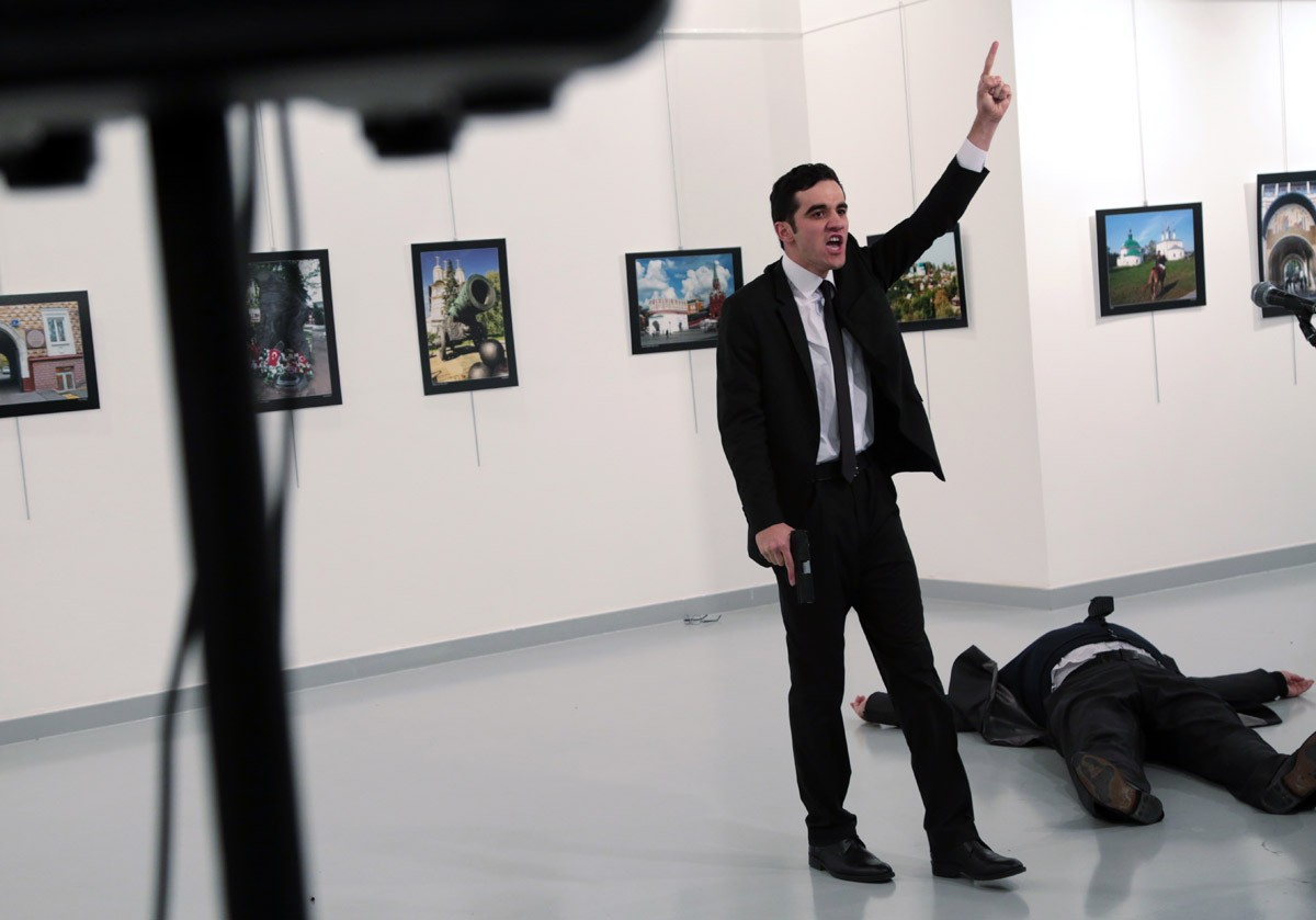 "Mevlut Mert Altintas, an off -duty police offi cer, shouts after shooting Andrei Karlov [right], the Russian ambassador to Turkey, at an art gallery in Ankara on Dec. 19. Turkey's president implicated a United States-based Muslim cleric in the killing of Russia's envoy to Turkey, saying the policeman who carried out the attack was a member of his ""terror organization""."