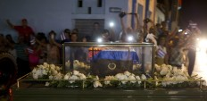 A small coffin covered by a Cuban flag with the ashes of the late Fidel Castro are carried on a trailer during a funeral procession that retraces the path of Castro's triumphant march into Havana nearly six decades ago, in La Esperanza, Cuba, Wednesday, Nov. 30, 2016. Castro's ashes have begun a four-day journey across Cuba from Havana to their final resting place in the eastern city of Santiago.