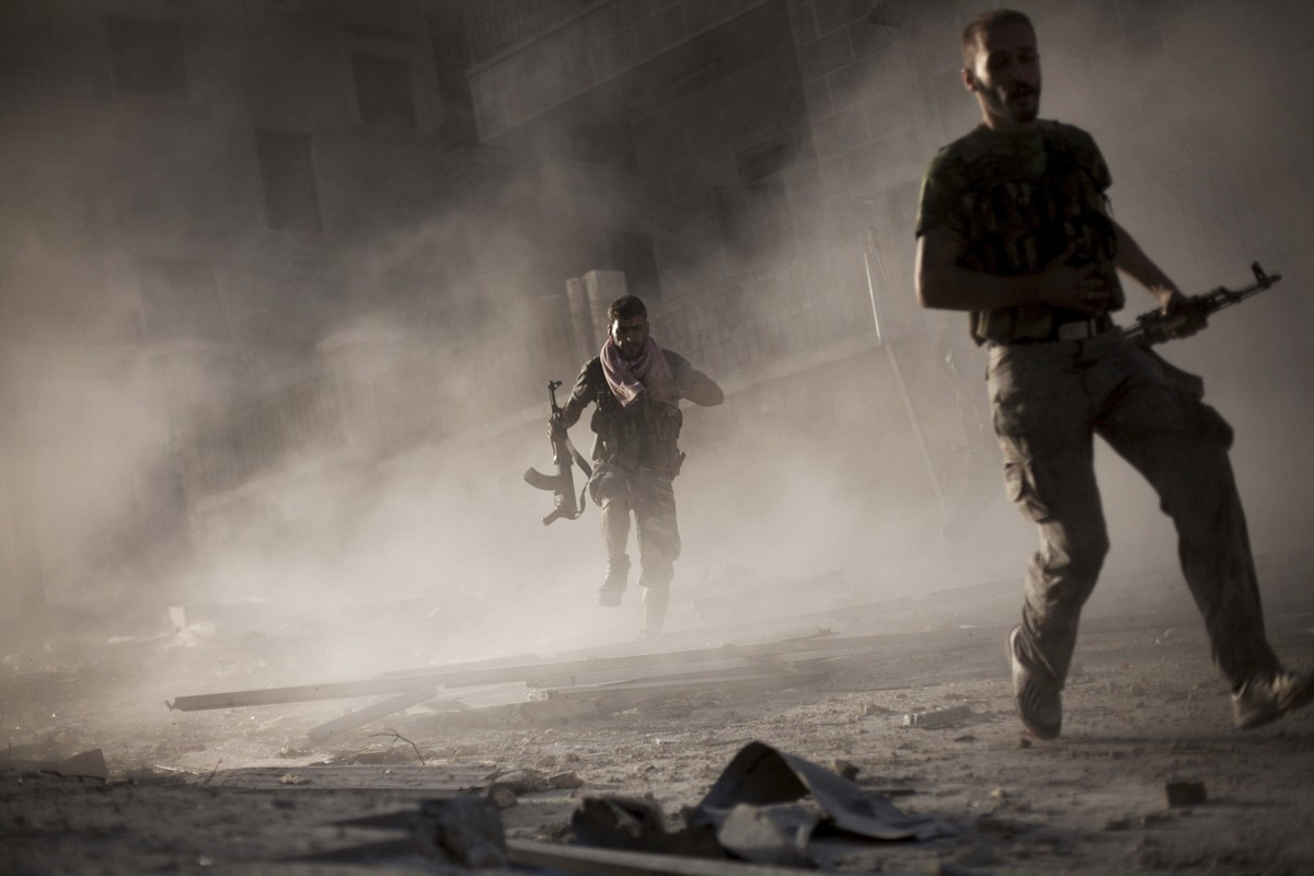 Free Syrian Army fighters run away after attacking a Syrian Army tank during fighting in the Izaa district in Aleppo, Syria, Friday, Sept. 7, 2012.
