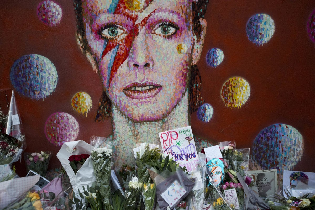 Tributes lie beneath a mural of singer David Bowie by artist Jimmy C in Brixton, South London, the United Kingdom, on Jan. 12. Bowie, the