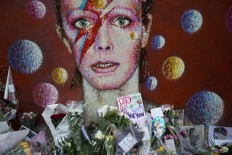 Tributes lie beneath a mural of singer David Bowie by artist Jimmy C in Brixton, South London, the United Kingdom, on Jan. 12. Bowie, the other-worldly musician who broke pop and rock boundaries with his nonconformity, striking visuals and a genre-spanning persona, and who created Ziggy Stardust, died at age 69 on Jan. 10.