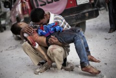 A man cries while holding the body of his son, killed by the Syrian Army, near Dar El Shifa hospital in Aleppo, Syria, Oct. 3, 2012.