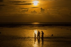 Three men watch the first sunrise of 2017 paint the world a glorious yellow at Sanur Beach in Bali on Sunday. JP/ Agung Parameswara