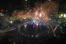 Thousand of Jakartans enjoy the fireworks at the Hotel Indonesia traffic circle in Jakarta on Saturday night. JP/Donny Fernando