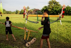 Two boys carry tengala and lampit, tools used in makepung lampit, a buffalo race on a wet paddy field in Jembrana. JP/ Agung Parameswara