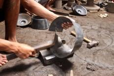A worker hammers a plate into a kenong percussion set. JP/Aditya Sagita