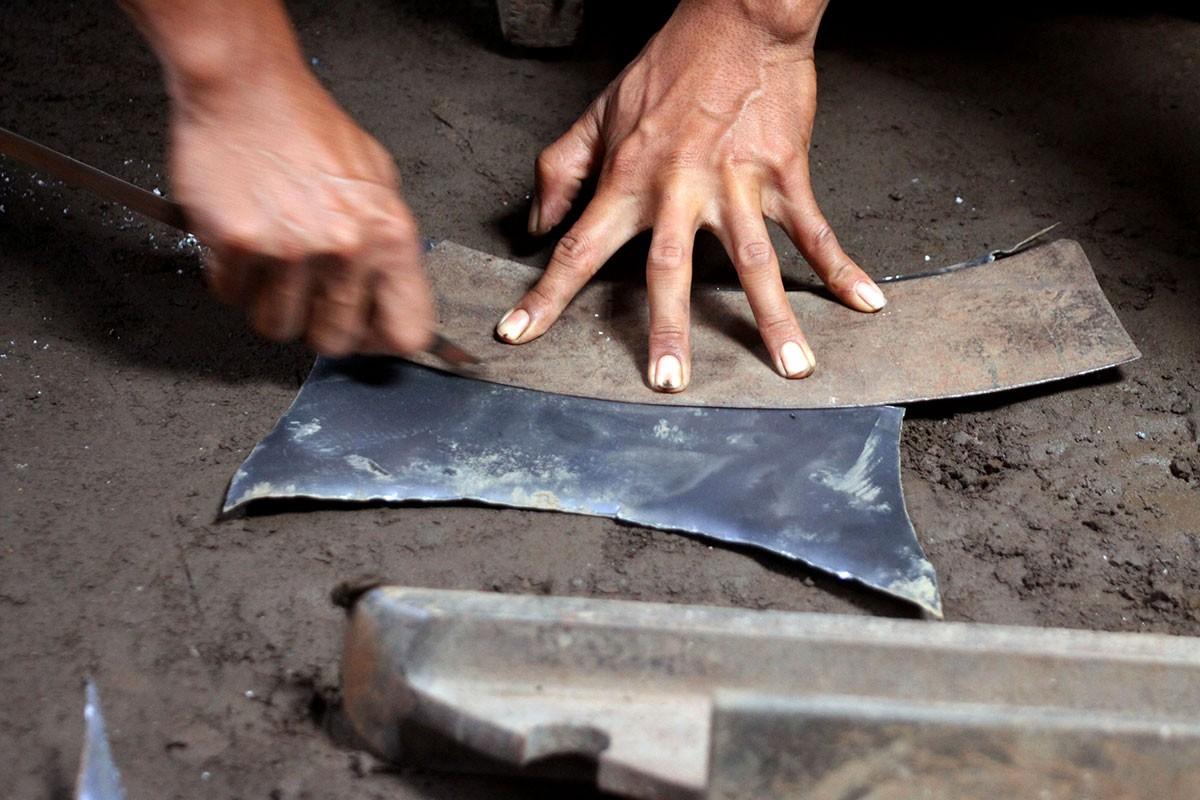 A man cuts a metal plate into a pattern for a kenong, a metal percussion set like a bonang, but bigger. JP/Aditya Sagita