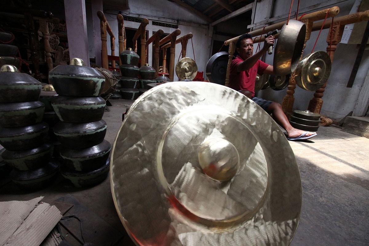 "Legiono checks the tune of a gong using a master gong, called the ""baboon"", as the benchmark. JP/Aditya Sagita"