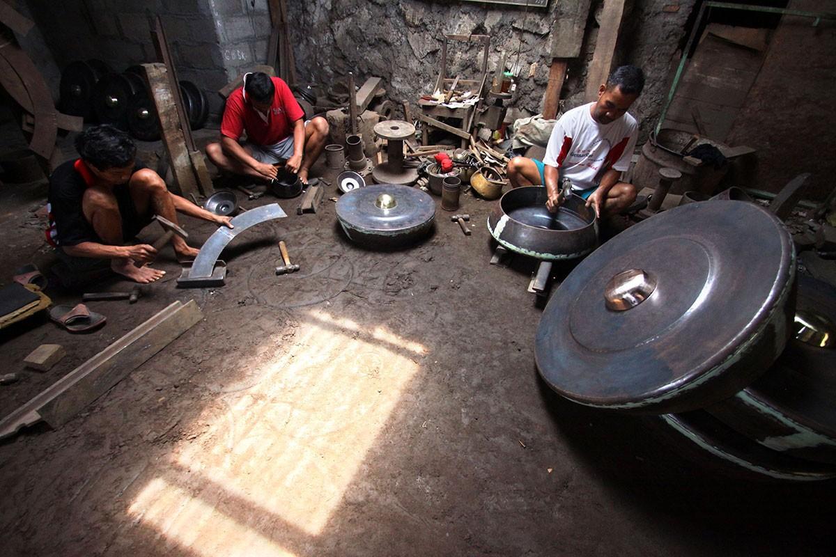 Three men cut and forge metal plates in the Daliyono Legiono workshop. JP/Aditya Sagita