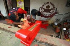 Workers paint a wooden rack for a bonang set red. JP/Aditya Sagita