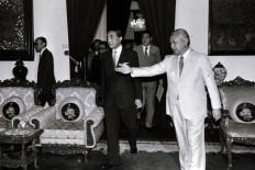 Soeharto [right] gestures to Nakasone [center] to take a seat at the palace in Jakarta ahead of a bilateral meeting on May 1, 1983. JP/Alex Lumy