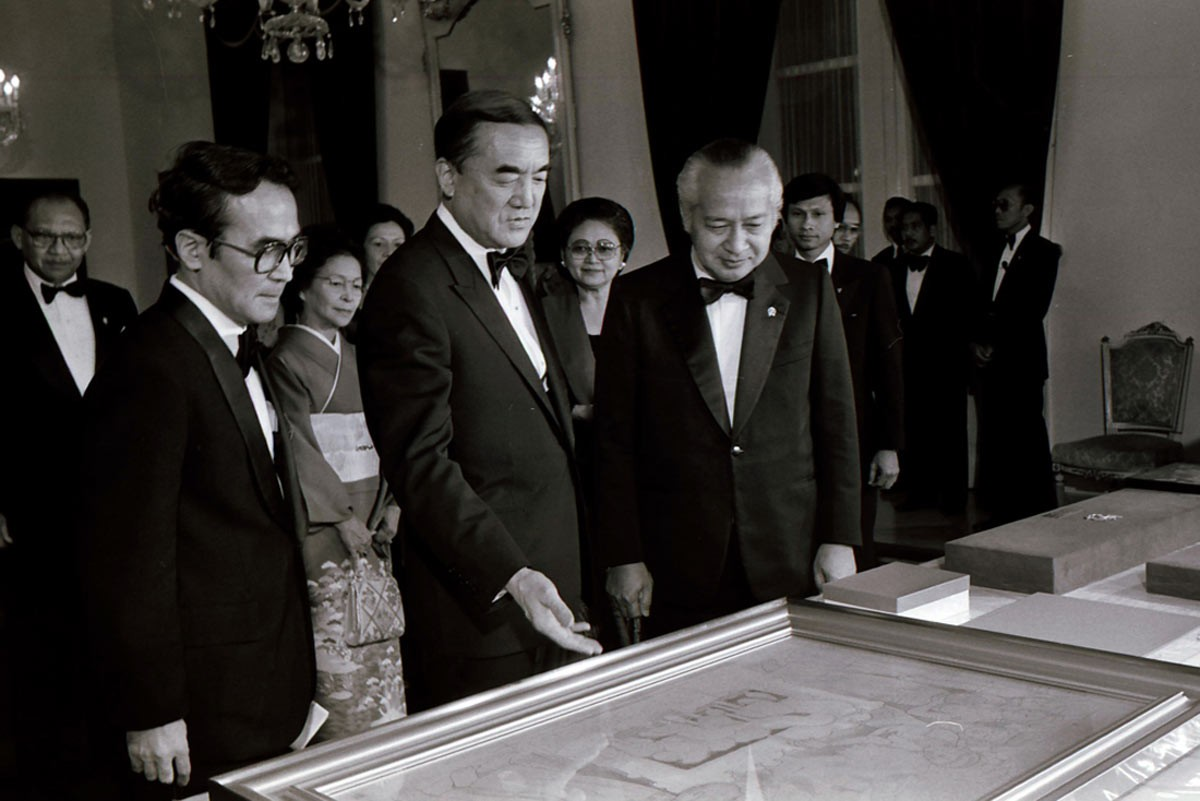 Soeharto [right] and Nakasone [center] prepare to attend a state dinner at the palace. JP/Alex Lumy
