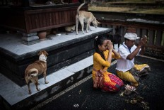 Devoted: Gung Dewi prays with her father in a temple in their village. JP/ Agung Parameswara