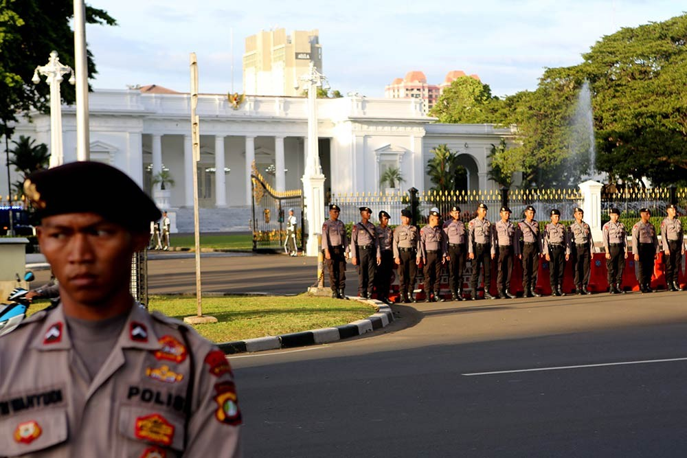 Policemen stand guard during the 10th commemoration of the Kamisan silent protest in front of the Presidential Palace in Jakarta on Jan. 19. The 477th Kamisan marks the 10th year since the first protest in 2007 asking the government to resolve past human rights violations. JP/Seto Wardhana.