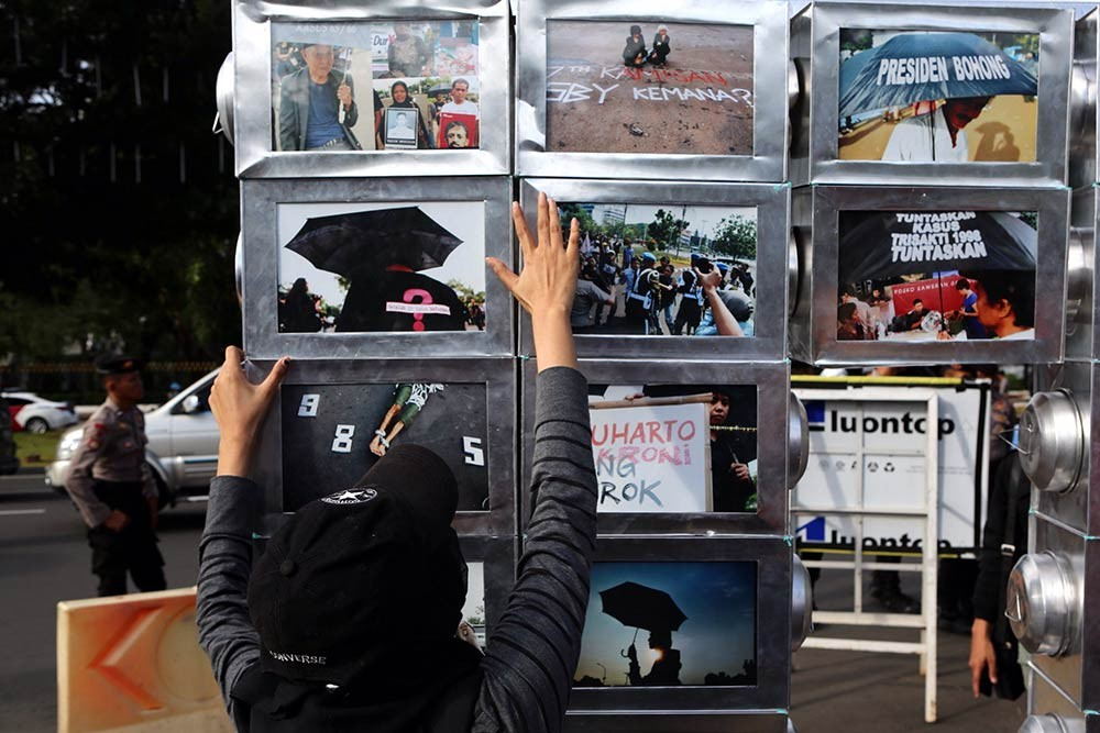 Activists stand next to a photo installation during the 10th commemoration of the Kamisan silent protest in front of the Presidential Palace in Jakarta on Jan. 19. The 477th Kamisan marks the 10th year since the first protest in 2007 asking the government to resolve past human rights violations. JP/Seto Wardhana.