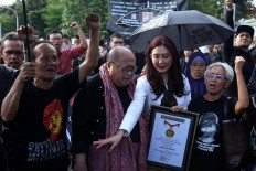 Jaya Suprana from the Indonesia Record Museum (MURI) hands a plaque to Maria Sumarsih during the 10th commemoration of the Kamisan silent protest in front of the Presidential Palace in Jakarta on Jan. 19. The 477th Kamisan marks the 10th year since the first protest in 2007 asking the government to resolve past human rights violations. JP/Seto Wardhana.