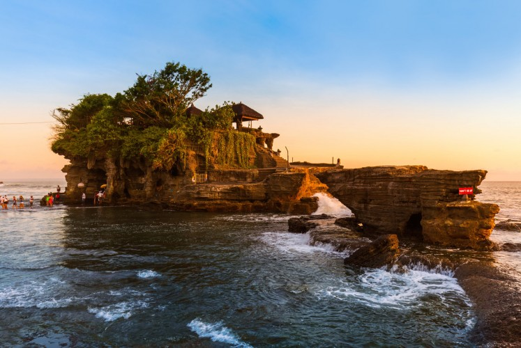 Tidal foam washes up against the natural rock base of Tanah Lot Temple.
