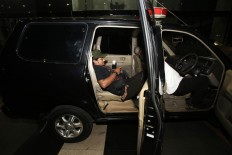 Journalists wait in a KPK car for Constitutional Court justice and bribery suspect Patrialis Akbar, who allegedly accepted bribes from a beef importing company, at the Corruption Eradication Commission office in Jakarta on Jan. 26. JP/ Dhoni Setiawan