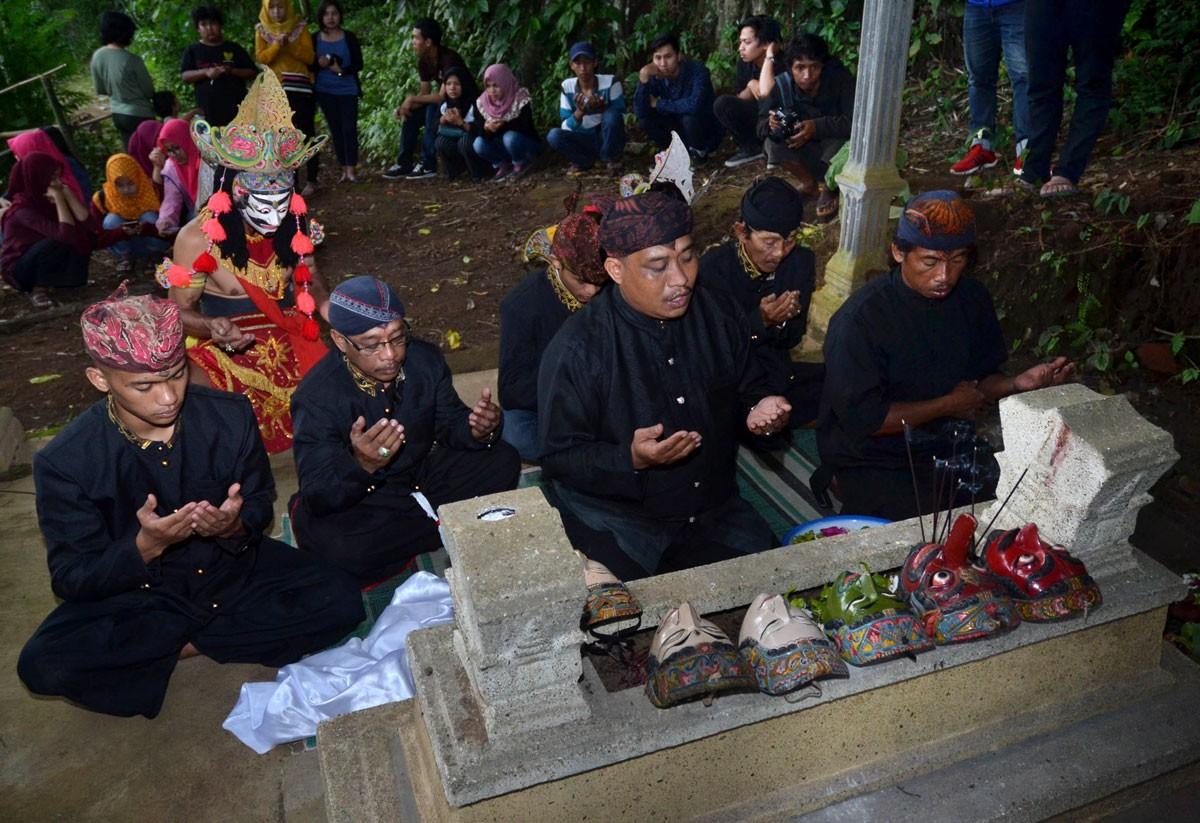 Suroso, one of Mbah Karimun's descendants, leads the prayer during Malangan mask dance ritual at Mbah Karimun grave, Pakiasji, Malang, East Java on Dec. 28. JP/ Aman Rochman
