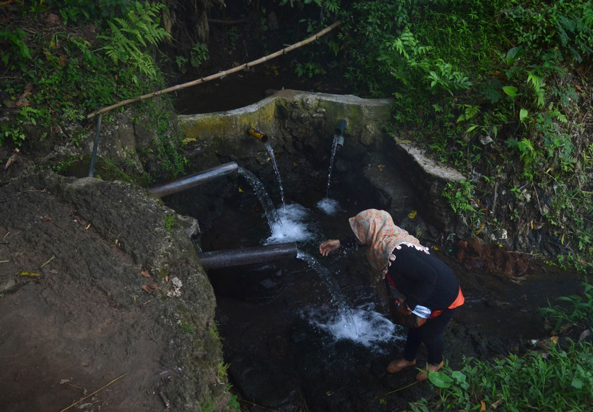 A woman washes her face at Sumber Lanang spring during Malangan mask dance ritual in Malang, East Java. JP/ Aman Rochman